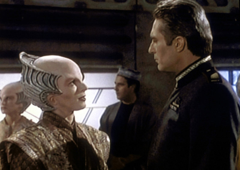 Minbari-Botschafterin Delenn (Mira Furlan, l.) erklärt Commander Sinclair (Michael O'Hare, r.), warum der Leichnam des Shai Alit überall da, wo sich Minbari aufhalten, öffentlich aufgebahrt wird. – Bild: ProSieben MAXX