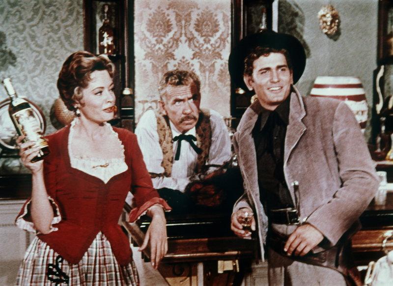 Weil Virginia City Geld braucht, versteigert Julia Bulette (Jane Greer, l.) eine Flasche Brandy, für die Little Joe (Michael Landon, r.) ein bedeutendes Gebot abgibt ... – Bild: Sat.1 Gold