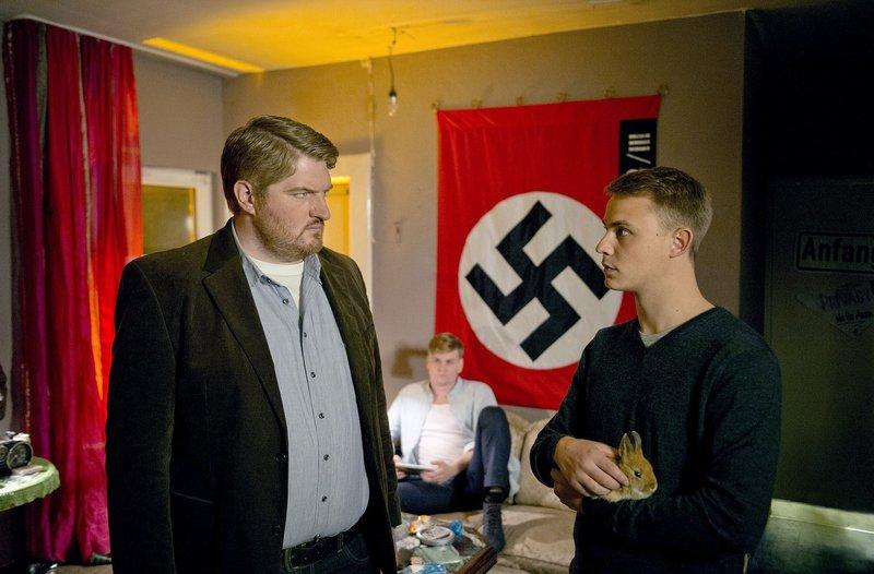 Hannes Krabbe (Marc Zwinz, l.) hat seinem Neffen Benni (Dennis Mojen, r.) einen Platz auf der Polizeiakademie besorgt. Als er ihn in seiner WG besucht, muss er zu seinem Entsetzen erkennen, dass er in die Neonazi-Szene abgerutscht ist. Im HG WG Mitbewohner Duffy Tacke (Karsten Jaskiewicz, M.) – Bild: ARD/Thorsten Jander