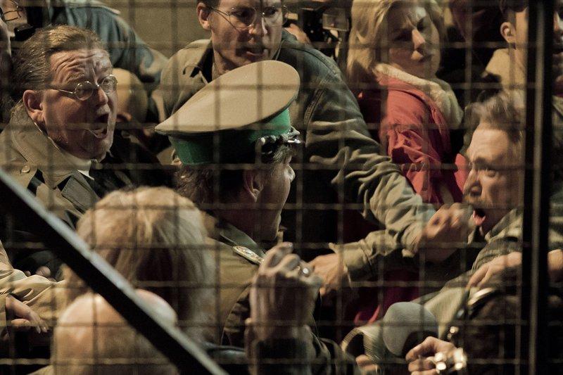 """Tragikomödie """"Bornholmer Straße"""". Erzählt wird die Geschichte um Oberstleutnant Harald Schäfer und die überraschende Wendung am Grenzübergang Bornholmer Straße in den letzten Stunden der DDR von Regisseur Christian Schwochow. Am Durchgang zur Passkontrolle kommt es zur Rangelei zwischen Wilfried Ernst (Peer-Uwe Teska), Uwe (Timo Jacobs) und weiteren DDR-Bürgern. – Bild: MDR/UFA FICTION/Nik Konietzny"""