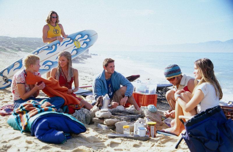 Nachdem Nina (Mira Bartuschek, l.) von Ralph (Brendan Kilcawley, M.) vor dem Ertrinken gerettet wurde, ruht sie sich in der Surferkommune aus. – Bild: Sat.1 Eigenproduktionsbild frei