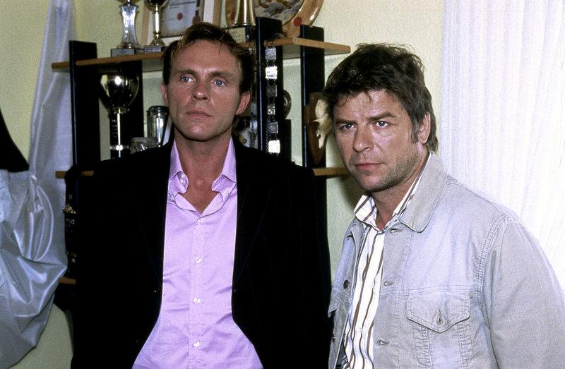 Sandra und Joachim Frings werden von Jupp (Uwe Fellensiek, r.) und Falk (Dirk Martens, l.) befragt. – Bild: Sat.1 Gold
