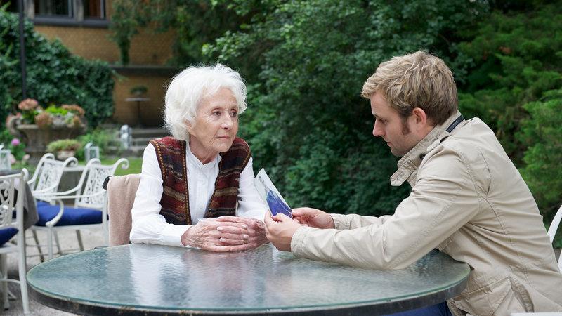 Obwohl Nils Theede (Jonas Laux) am wenigsten an die Geschichte der alten Dame (Rosemarie Fendel) glaubt, hat sie gerade zu ihm besonderes Zutrauen. Er erinnert sie an ihre Jugendliebe, und während des Gespräch kommen noch weitere Details zutage. – Bild: ZDF
