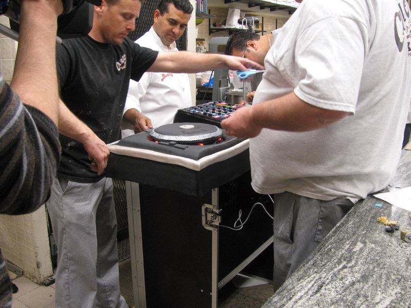 Buddy, Joey, Frankie, Mauro work on DJ Cake. Tune into TLC this October for brand new episodes following Buddy Valastro, one of America?s most successful and renowned cake artists and the boss of ?Carlo's City Hall Bake Shop? in Hoboken, New Jersey. With a team of bakers that include his mother, four older sisters and three brothers-in-law, life is never dull! See Buddy and the crew take on one of their most difficult cake builds yet - a cake that must represent houses from around the world for Century 21's 40th anniversary; and to add to the challenge - the cake must feed over 4000 employees! Buddy also makes a surprise cake for Anthony that looks like a DJ set up, complete with lights and moving turntables!; and is asked to create a giant Bumblebee cake to help promote the blockbuster movie Transformers 3. The team are asked to make a bowling cake that leads to a ?boys versus girls? match on the lanes; and finally Buddy gets news that there are complications at his new factory. – Bild: Copyright: Discovery Communications, Inc. EMEA/UK Editorial Use Only. - Discovery Networks Picture Publicity. This picture may be used solely for Discovery Networks programme publicity purposes. May b