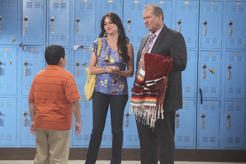 Gloria (Sofia Vergara) und Jay (Ed O'Neill, re.) bringen Manny (Rico Rodriguez) den vergessenen kolumbianischen Poncho in die Schule. – Bild: Comedy Central