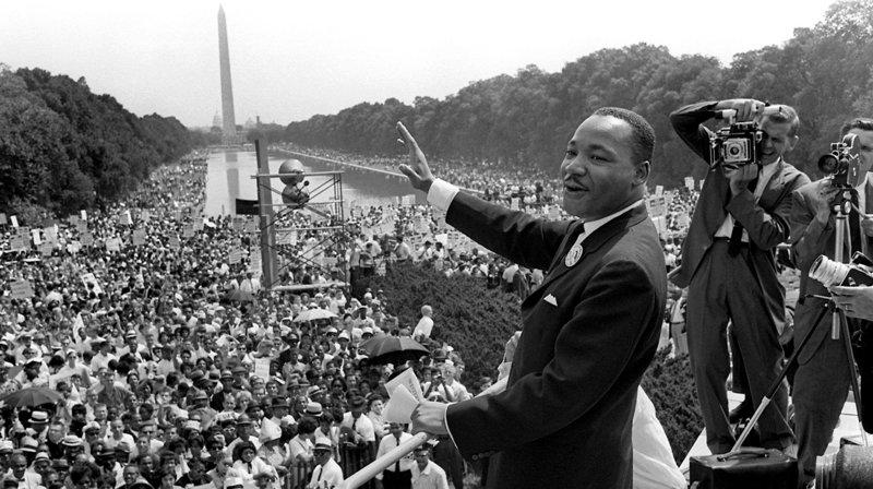 """Der US-Bürgerrechtler Martin Luther King winkt von der Lincoln Gedächtnisstätte in Washington aus seinen Anhängern zu (im Hintergrund das Washington Monument). Über 100000 farbige US-Bürger hatten, unterstützt durch zahlreiche weiße Mitbürger, mit einem """"Marsch auf Washington""""für ihre Rechte demonstriert. Während der großen Abschlußkundgebung vor dem Denkmal des früheren US-Präsidenten Abraham Lincoln forderte der Bürgerrechtler in seiner historischen Rede """"I have a dream"""" ein Amerika ohne Rassismus. Der am 4.4.1968 in Memphis ermordete Martin Luther King ist bis heute der einzige Farbige, dessen Geburtstag in den USA als Nationalfeiertag begangen wird. – Bild: WDR/dpa"""