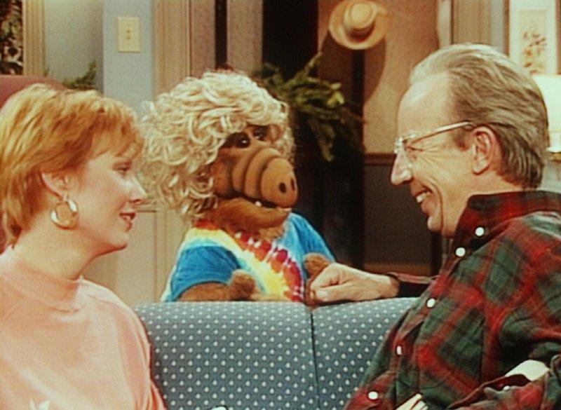 Mit Perücke getarnt will sich Alf (M.) auf die Straße wagen. Willie (Max Wright, r.) und Kate (Anne Schedeen, l.) finden diese Idee sehr erheiternd. – Bild: TM+© Warner Bros. Lizenzbild frei