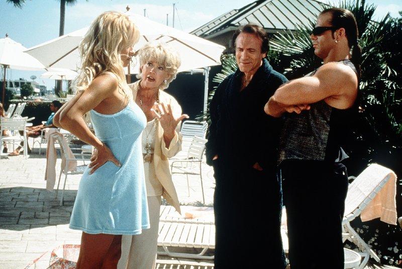 C. J. (Pamela Anderson, l.) ist fest entschlossen, ihre Mutter Shelley (Connie Stevens, 2.v.l.) vor ihrem Ex-Freund Tony Blanton (David Groh, 2.v.r.) und seinem Leibwächter Vinnie (Shawn Michaels, r.) zu schützen. – Bild: Nitro.