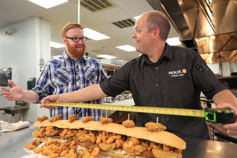 """Koch Jason (r.) misst für Josh (l.) gerne noch einmal nach: das """"BL-Titan Sandwich"""" erstreckt sich tatsächlich über einen ganzen Meter. – Bild: 2017,Television Food Network, G.P. All Rights Reserved"""