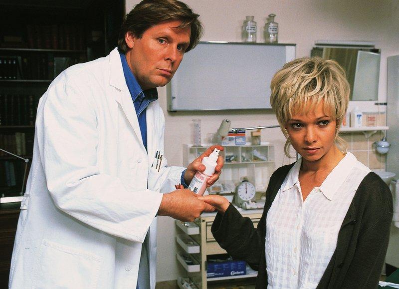 Dr. Stefan Frank (Sigmar Solbach) behandelt eine Schnittverletzung bei Nicole Wandler (Iris Junik). – Bild: RTLplus