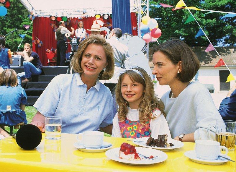 """Marijke Amado moderiert auf dem Kinderfest eine """"Kinder-Playback-Show"""" für die Waisenkinder. Bea (Isabelle von Siebenthal, r.) und Iris (Jana Kilka, M.) freuen sich riesig über den prominenten Gast! – Bild: RTLplus"""