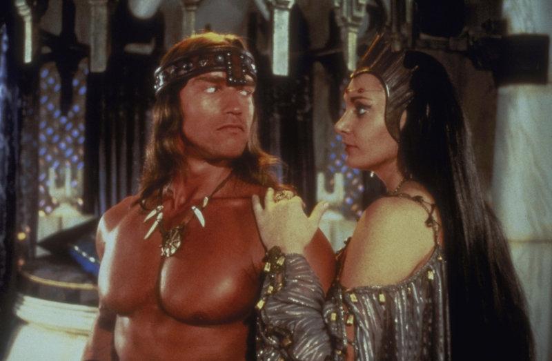 Die schöne Königin Taramis (Sarah Douglas, r.) beauftragt Conan (Arnold Schwarzenegger, l.) mit der Suche nach einem geheimnisvollen Schatz. Als Dank für seine Hilfe verspricht sie ihm, seine tote Gefährtin wieder zum Leben zu erwecken ... – Bild: Universal Pictures Lizenzbild frei