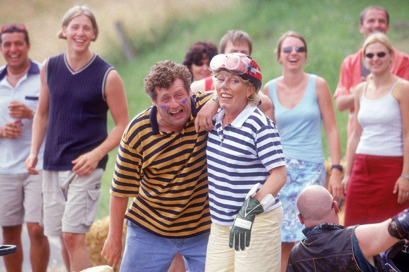 Hier die zwei stolzen Gewinner des Seifenkistenrennens: Die glückliche Fahrerin Uschi (Antje Lewald, vo.r.) und daneben der etwas erschöpfte Benno (Willi Thomczyk), der seiner Uschi zu Fuß ins Ziel gefolgt ist. – Bild: RTLplus