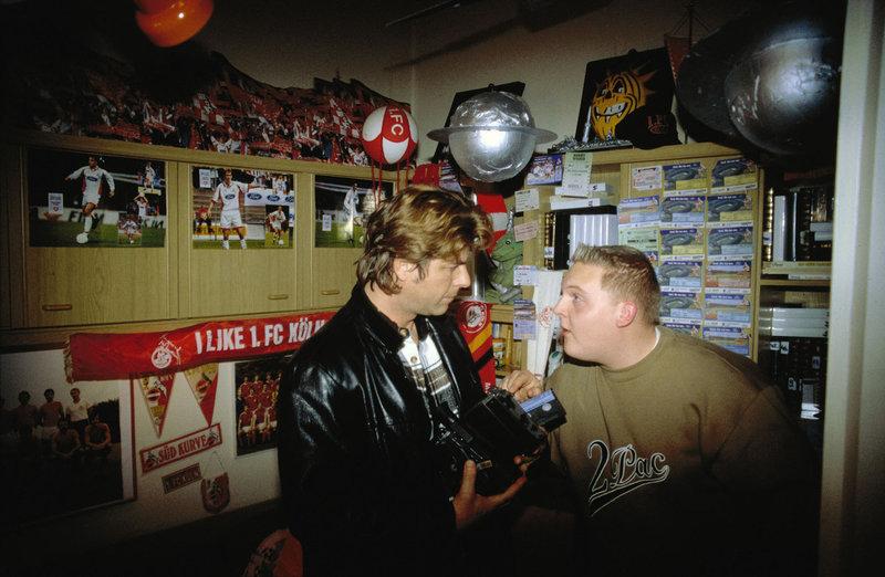 Jupp (Uwe Fellensiek, l.) unterhält sich mit Robbie (Axel Stein, r.) über das Spiel, das er auf Videokassette aufgezeichnet hat. – Bild: Sat.1 Gold
