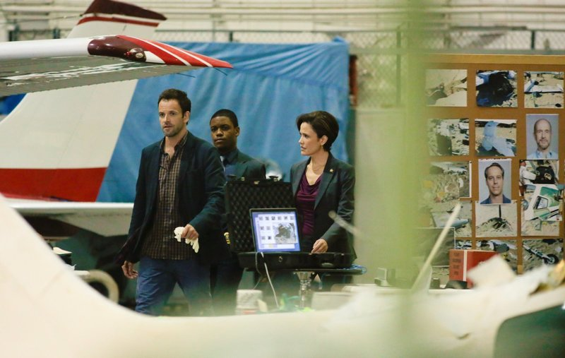 Sherlock (Jonny Lee Miller, left) and Detective Bell (Jon Michael Hill, center) try to prove that one of people whose body was found in the wreckage of small plane crash was actually killed before the plane went down. Also pictured is Reiko Aylesworth as Miranda Molinari. – Bild: Giovanni Rufino / Die Verwendung ist nur bei redak / CBS Entertainment / © CBS Television Studios
