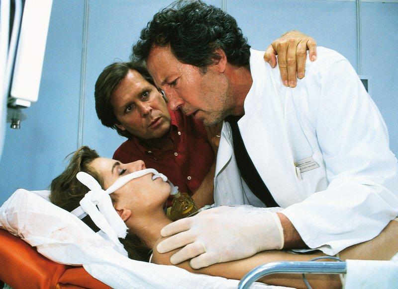 Dr. Stefan Frank (Sigmar Solbach, Mi.) und Chefarzt Dr. Ulrich Waldner (Hartmut Becker) kümmern sich um den Notfall Vera Junghans (Karin Thaler). – Bild: RTLplus