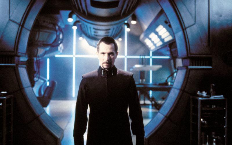 Der Wissenschaftler Dr. Smith (Gary Oldman) programmiert den Arbeitsroboter an Bord des Raumschiffs so um, dass dieser die Robinsons kurz nach dem Start töten und das Raumschiff vernichten soll... – Bild: RTL II