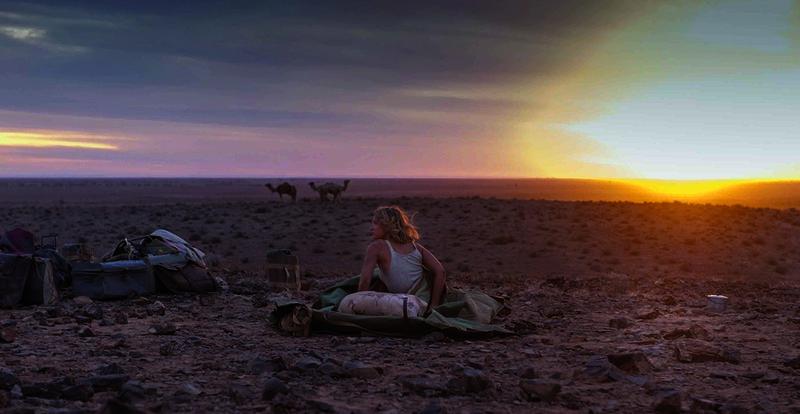 """Die junge Robyn Davidson (Mia Wasikowska) will 2.700 Kilometer durch die australische Wüste bis an die Küste des Indischen Ozeans wandern, begleitet nur von einem Hund und vier Kamelen. Da Robyn das nötige Geld fehlt, arbeitet sie mehrere Monate für einen Kamelhändler. Als sie den Fotografen Rick kennenlernt, will der über ihre Reise eine Reportage für das Magazin """"National Geographic"""" realisieren. Robyn willigt ein und die beiden machen sich auf den langen, abenteuerlichen Weg. – Bild: Servus TV"""