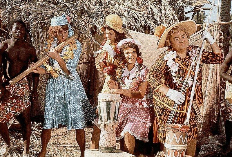"""Nach einer Notlandung im Dschungel muessen die Musiker der Kapelle """"Die Sonnyboys"""", als Frauen verkleidet, um ihr Leben musizieren. Pit (Udo Juergens, 2.v.l.), Paul (Wolfgang Jansen, 3.v.l.), Gus (Gus Backus, 2.v.r) und Hyacinth (Kurt Grosskurth, r.) sind unter Kopfjaeger geraten, die allerdings nur an maennlichen Koepfen interessiert sind. – Bild: ORF"""