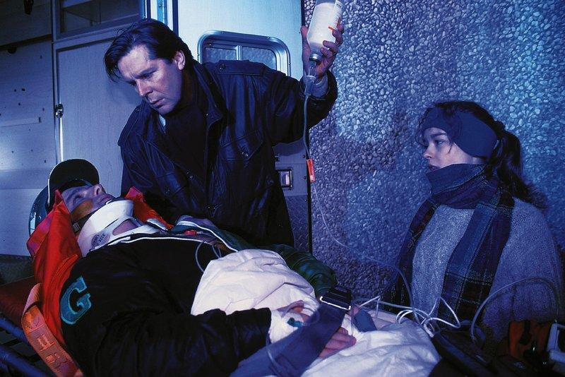 Dr. Stefan Frank (Sigmar Solbach) kümmert sich nach dessen Sturz um den verletzten Sulkeyfahrer Ralph Portmann (Jens Peter Nünemann, lieg.). Portmanns Schwester Andrea (Janina Flieger) weicht nicht von seiner Seite. – Bild: RTL Passion