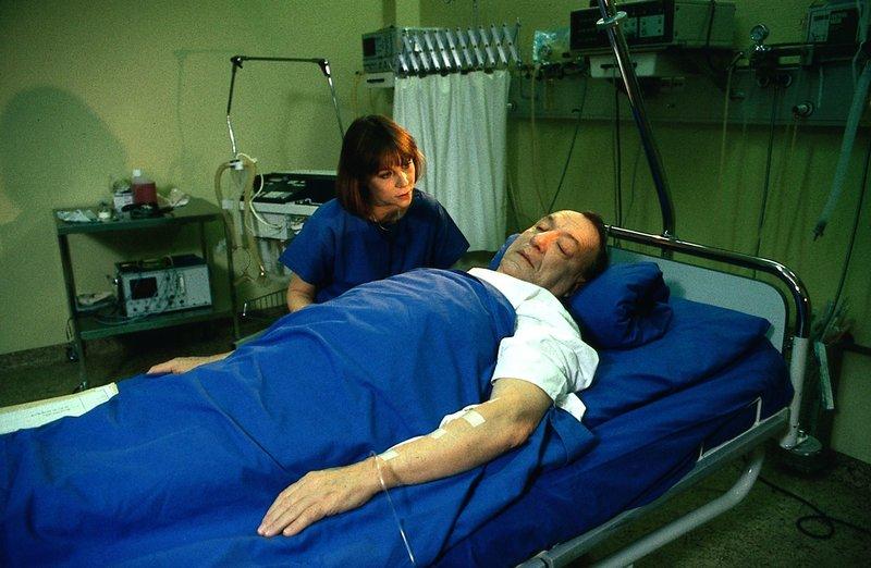 13. Frau Dr. Plessers (Verene Peter) ist zur Stelle, als Herr Weidle (Ulrich Matschoss), der sich für todkrank hält, nach der Operation aus der Narkose erwacht. – Bild: Thomas Waldhelm