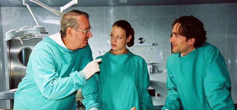 Dr. Graf (Gerhard Zemann, l.) erklärt Niki (Elke Winkens, M.) und Marc (Alexander Pschill, r.) die genaueren Umstände, die zum Tod der jungen Frau führten. – Bild: Sat.1 Gold