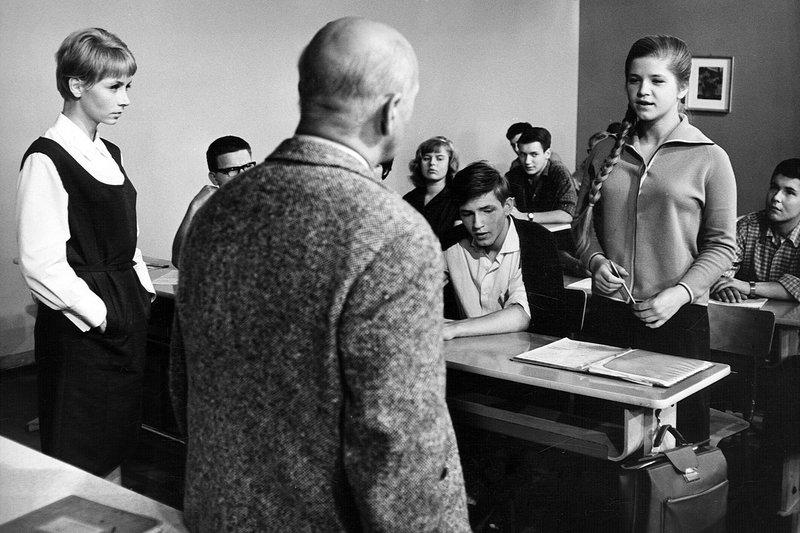 Jutta Hoffmann (Karla, Lehrerin) steht seitlich vor Schulklasse; ein Gast (Journalist, von hinten) ist der Klasse zugewandt; eine Schülerin stehend (redend) – Bild: MDR/PROGRESS/Eberhard Daßdorf