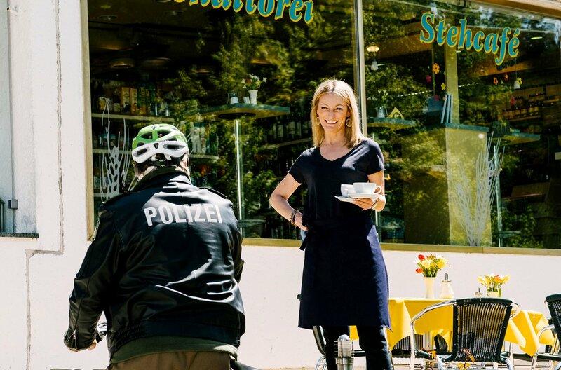 Barbara Hansen (Monika Gruber, r.) begrüßt Girwidz (Michael Brandner, l.) in ihrem Café. – Bild: ARD/TMG/Arvid Uhlig