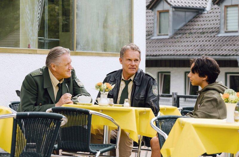 Hubert (Christian Tramitz, M.) und Girwidz (Michael Brandner, l.) wollen Kai Tennholt (Yanis Scheurer, r.) als verdeckten Ermittler anheuern. – Bild: ARD/TMG/Emanuel A. Klempa