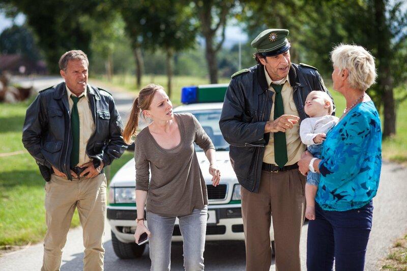 Lena Gründing (Katherine Brand, 2. von links) sucht mit der Hilfe von Hubert (Christian Tramitz, links) und Staller (Helmfried von Lüttichau, 2. von rechts mit Komparsin) nach ihrem verschwundenen Baby. – Bild: ARD/BR/TMG/Christian Hirschhäuser