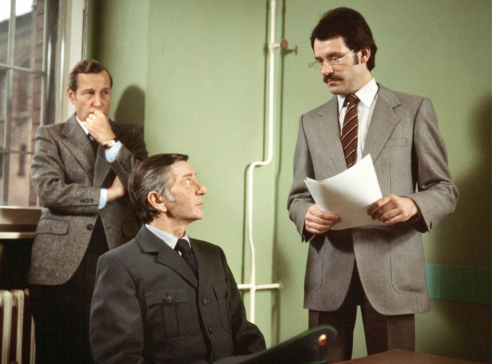 Rudi Jakobs (Herbert Stass) wird von dem Staatsanwalt (Jürgen Draeger) verhört. Kommissar Haferkamp (Hansjörg Felmy) fragt sich, ob Jakobs bei dem Gefängnisausbruch einen der Häftlinge fahrlässig erschossen haben könnte. – Bild: WDR
