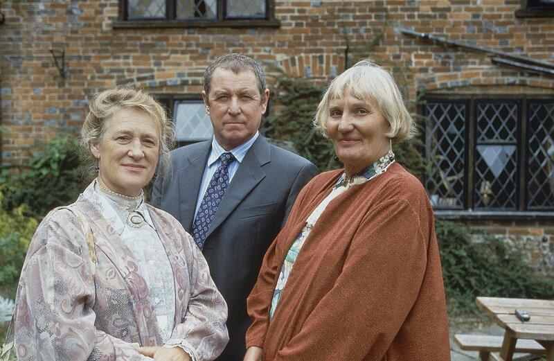 Inspector Barnaby (John Nettles, M.) erfährt bei seinen Ermittlungen in Midsomer Parva interessante Details von den Schwestern Alice (Merelina Kendall, l.) und Marian Leonard (Charmian May, r.), die das Postamt des Ortes führen. – Bild: ZDF und All3Media/All3Media