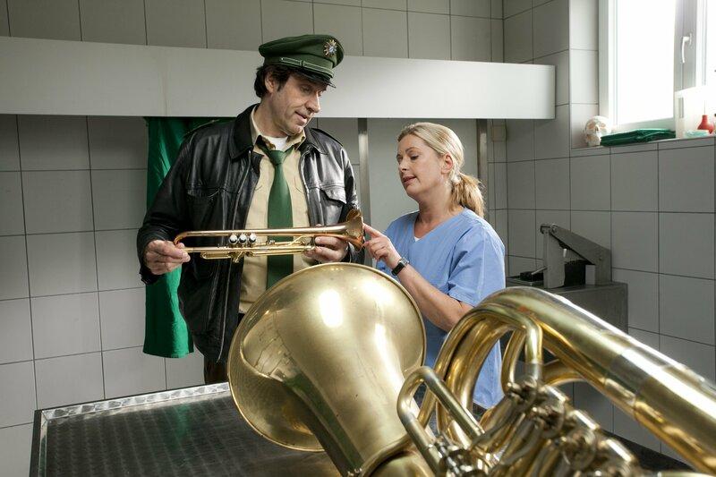 Dr. Anja Licht (Karin Thaler, rechts) erklärt Staller (Helmfried von Lüttichau), dass die Trompete die Tatwaffe war. Mit dieser wurde sechs Mal auf das Opfer eingeschlagen. – Bild: TMG / Chris Hirschhäuser