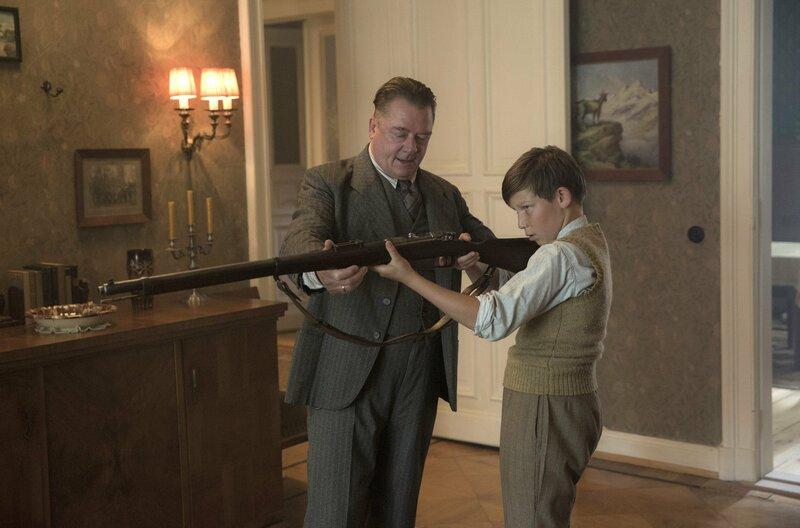Wolter (Peter Kurth) erklärt Helgas Sohn Moritz (Ivo Pietzcker) das Gewehr. – Bild: ARD Degeto/X-Filme/Beta Film/Sky Deutschland/Frédéric Batier