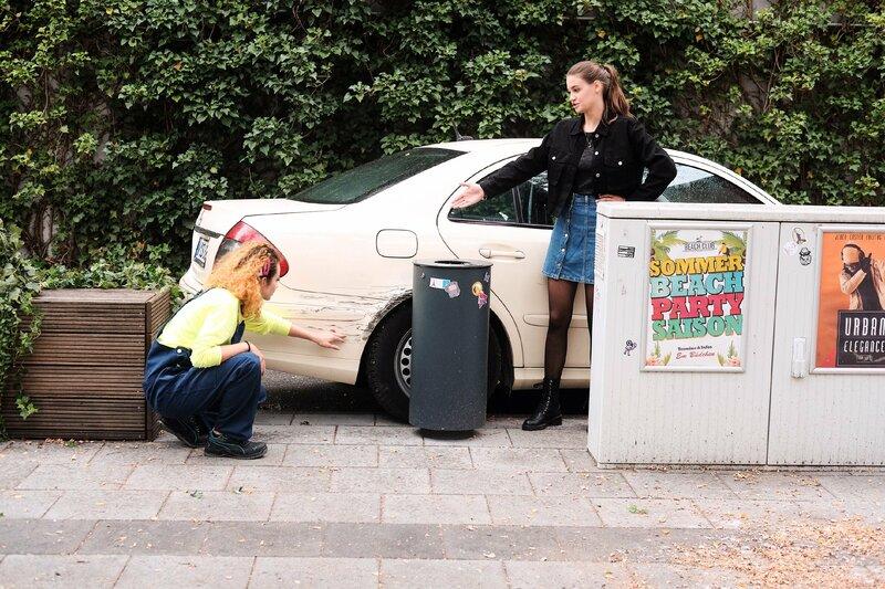 Leni (Josephine Becker, r.) muss befürchten, dass Paco von ihrem selbstverschuldeten Unfall erfährt. Nika (Isabelle Geiss) schaut sich den Schaden an. – Bild: TVNOW