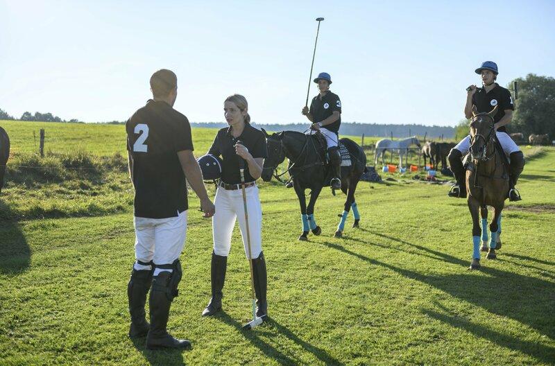 Um nach Franzi suchen zu können, bittet Tim (Florian Frowein, l.) Amelie (Julia Gruber, 2.v.l.), bei Polo-Turnier für ihn einzuspringen (mit Komparsen). – Bild: ARD/Christof Arnold