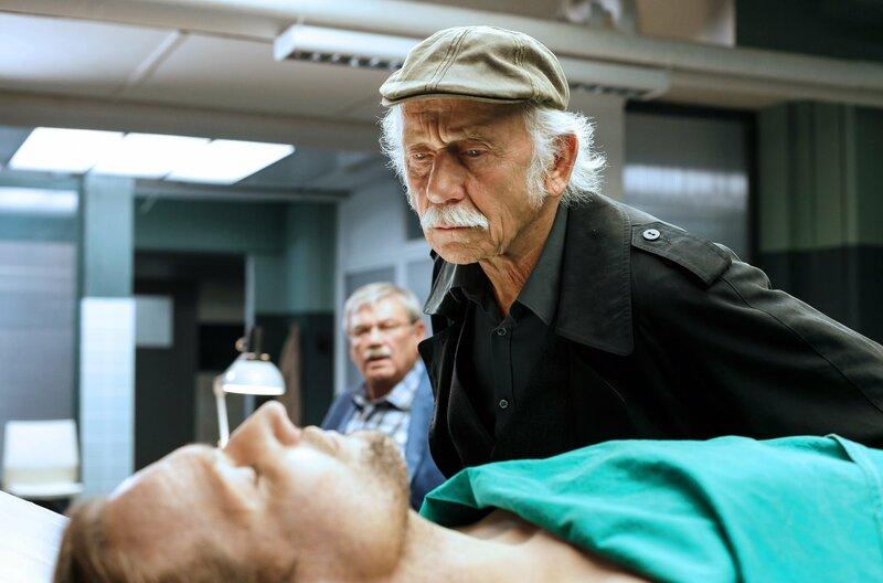 Dr. Jamm (Michael Kors, l.) ist ermordet worden. Edwin Bremer (Tilo Prückner, r.) mustert die Leiche, Kollege Günter Hoffmann (Wolfgang Winkler, im HG) hält sich im Hintergrund. – Bild: WDR/ARD/Kai Schulz
