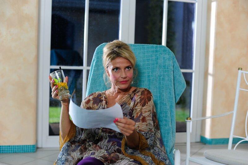 Die Schlagersängerin Andrea Manninger (Ursula Gottwald) bekommt von Hubert und Staller ein Foto überreicht, auf dem das Mordopfer Fabian Pfeifer nackt in ihrem Garten zu sehen ist. – Bild: TMG / Chris Hirschaeuser