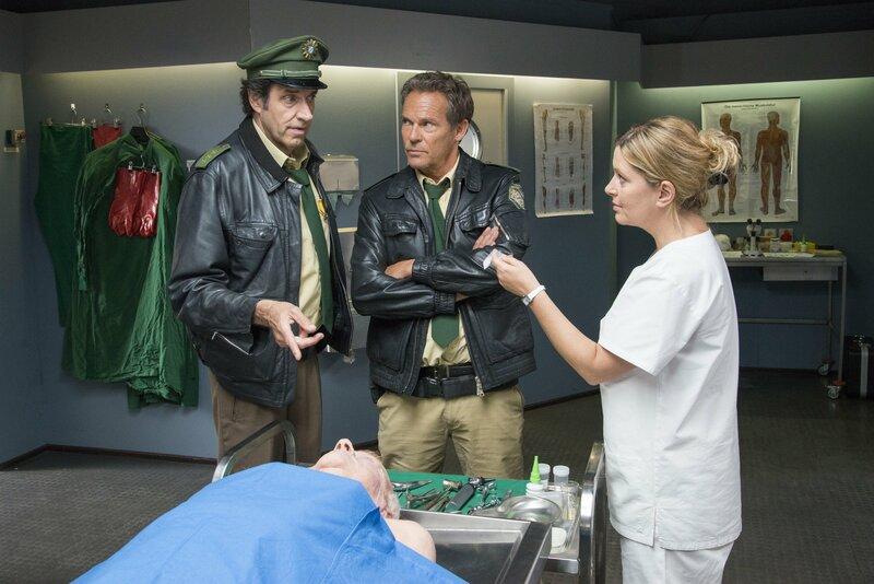 Dr. Anja Licht (Karin Thaler, rechts) hält Hubert (Christian Tramitz, Mitte) und Staller (Helmfried von Lüttichau) ein Päckchen Drogen hin, das sie bei der Leiche des Polizeipräsidenten gefunden hat. – Bild: TMG / Marco Meenen