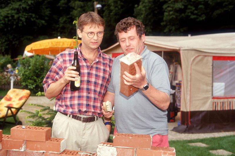 Benno (Willi Thomczyk, re.) präsentiert seinem Freund Lothar (Rene Heinersdorff) stolz sein selbst gebautes Geschenk - einen neuen Grill. Doch Lothar ist nicht so begeistert - er wollte genau hier eigentlich einen Laufstall für Max aufstellen... – Bild: RTLplus