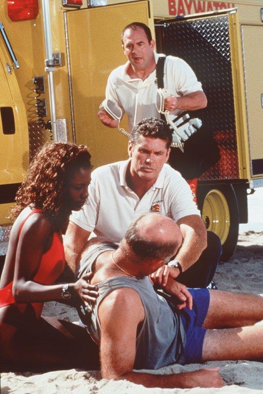 Ein Jogger hat schlapp gemacht. Sheryl (Ingrid Walters) und Mitch (David Hasselhoff, M.) stellen fest, dass dem Mann nichts fehlt. Sehr zum Leidwesen von Ed, der gern ein neues Beatmungsgerät verkauft hätte. – Bild: Nitro.