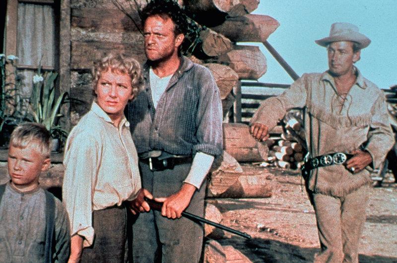 Die Familie Starrett (Brandon De Wilde, links; Jean Arthur, 2. von links; Van Heflin, 3. von links) ist besorgt wegen Rykers Bande, die sie bedroht. Shane (Alan Ladd, rechts) beobachtet ruhig und selbstsicher das Geschehen. – Bild: ZDF und Loyal Griggs