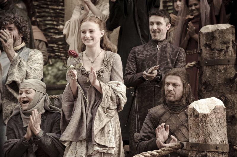 Ein Turnier findet statt und Sansa (Sophie Turner, Mitte) ist begeistert. Auch ihr Vater Ned Stark (Sean Bean, re.) und 'Kleinfinger' Baelish (Aidan Gillen, 2.v.re.) finden sich unter den Zuschauern. – Bild: RTL II