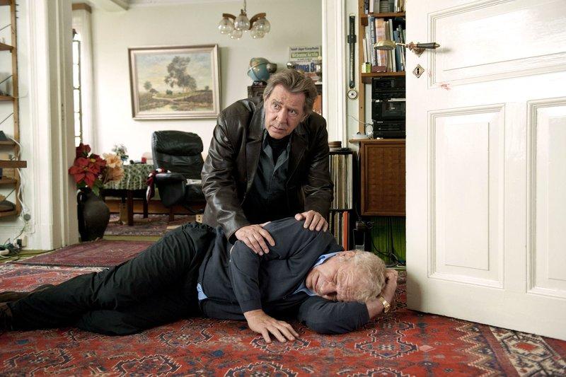 Als Dirk Matthies (Jan Fedder) bei seinem alten Freund Walter Bansemann (Michael Hanemann, liegend) vorbeischaut, findet er ihn ohnmächtig in seinem Wohnzimmer. – Bild: ARD