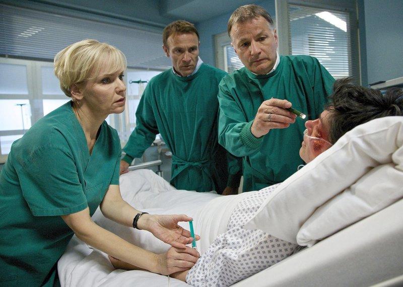 """ARD/MDR IN ALLER FREUNDSCHAFT FOLGE 663, """"Aus allen Wolken"""", am Dienstag (21.10.14) um 21:00 Uhr im ERSTEN. Elena Eichhorn (Cheryl Shepard, re.) gerät in Panik, als sie plötzlich Doppelbilder sieht. Dr. Roland Heilmann (Thomas Rühmann, re. hi.) und Dr. Kathrin Globisch (Andrea Kathrin Globisch, li.) befürchten eine baldige Erblindung, können die dafür notwendige Gesichtsoperation jedoch erst nach Elenas Wirbelkörperbruch-OP durchführen. Elena bricht in Tränen aus und richtet ihre verzweifelten Worte an Dr. Martin Stein (Bernhard Bettermann, li. hi.). – Bild: rbb"""