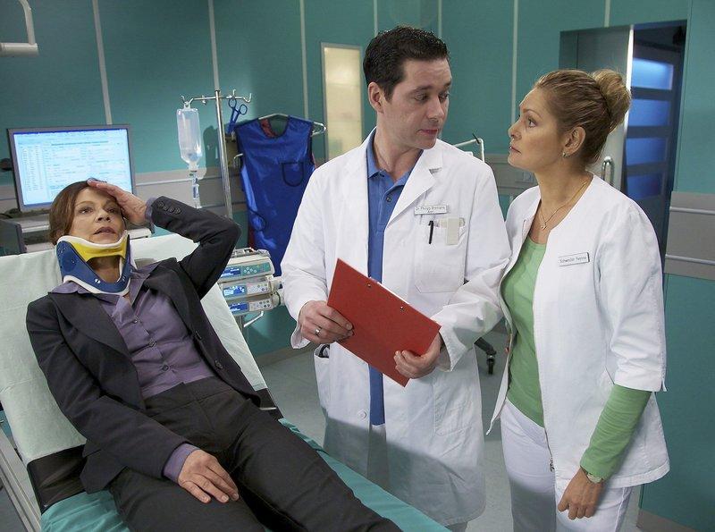 Als Prof. Ursula Rakenius (Angela Roy, links) nach einem Autounfall erneut in die Sachsenklinik eingeliefert wird, nimmt sie Dr. Philipp Brentano (Thomas Koch) auf. Die CT-Bilder zeigen keine Verschlechterung ihres Zustandes, doch Rakenius gibt an, ein Bein nicht mehr zu spüren. Dr. Brentano und Schwester Yvonne (Maren Gilzer, rechts) wissen, dass das eine sofortige OP nötig machen würde. Schwester Yvonne rät Philipp, Dr. Heilmann zu konsultieren, da dieser eine Operation abgelehnt hat. Nun ist Rakenius jedoch Philipps Patientin und er entscheidet sich für eine Operation. – Bild: Bayerisches Fernsehen