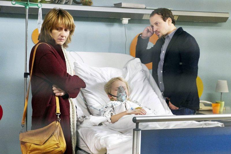 Meike Bender (Jennipher Antoni, li.) wollte ihrem Mann Ingo (Max Hoppe, re.) den Klinikaufenthalt ihres gemeinsamen Sohnes Luis (Georg Arms, mi.) verschweigen. Sie haben sich getrennt, weil Meikes Überfürsorge für Luis zum Mittelpunkt ihrer Beziehung wurde. Nun nähern sie sich langsam wieder an, bei einem Treffen bekommt Meike einen Anruf aus der Sachsenklinik. Nun weiß Ingo, dass Luis schon wieder zu einer Untersuchung beim Arzt ist. Auch die Ärzte sind ratlos, Dr. Brentano vermutet sogar bei der Mutter ein Münchhausen-Stellvertreter-Syndrom. Doch dann geht es Luis tatsächlich schlechter. – Bild: MDR/Saxonia Media Filmproduktion/Wernicke