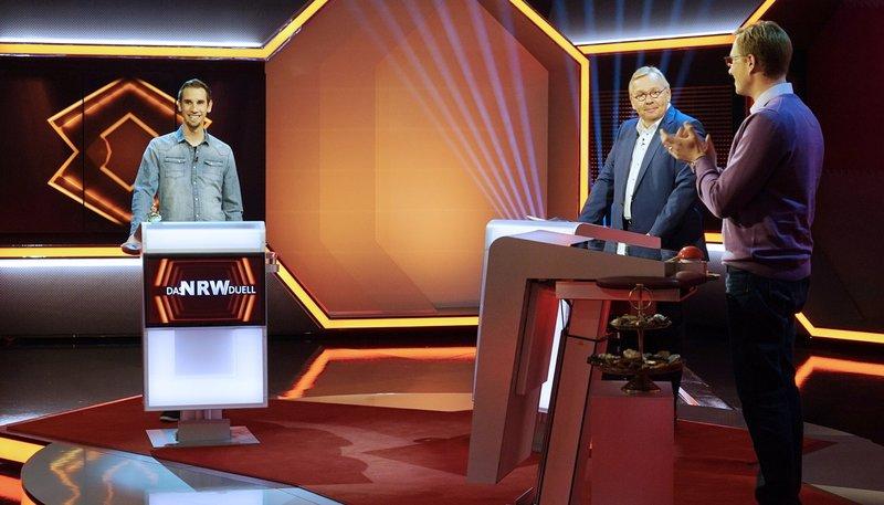Moderator Bernd Stelter (Mitte) mit den Kandidaten Björn Steffens (l), Weihnachtskurzfilmer, und Andreas Klein, Printenbäcker. – Bild: WDR