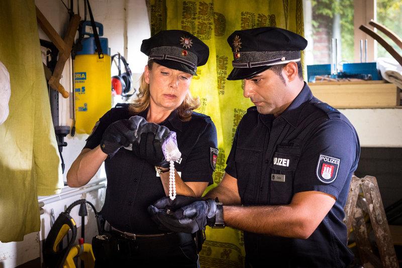 Claudia (Janette Rauch) und Tarik (Serhat Cokgezen) finden den Schmuckbeutel, den der Einbrecher zurückgelassen hat, als ihn der Wachhund angriff. – Bild: ZDF
