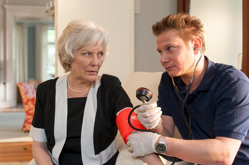 Notarzt Haase (Fabian Harloff) versorgt die zusammengebrochene Elvira Wildberger (Marie Anne Fliegel), doch diese weigert sich beharrlich ins EKH zu gehen. – Bild: ZDF und Boris Laewen